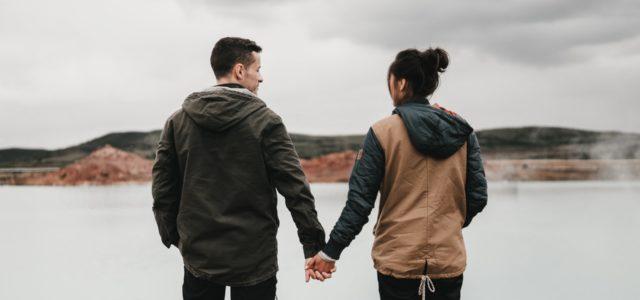 Par, der holder hinanden i hånden på straden